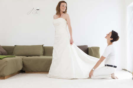 Designer fitting wedding gown on client LANG_EVOIMAGES