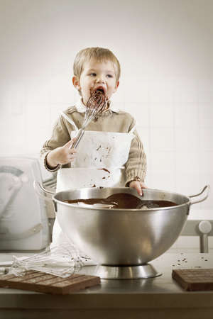 mischeif: Boy licking whisk in kitchen LANG_EVOIMAGES