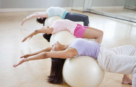 20 years old: Women on exercise balls in gym class LANG_EVOIMAGES