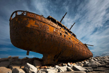 perilous: Rusted shipwreck on rocky beach LANG_EVOIMAGES