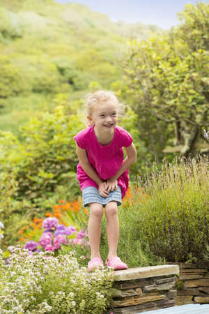 Smiling girl playing in garden LANG_EVOIMAGES