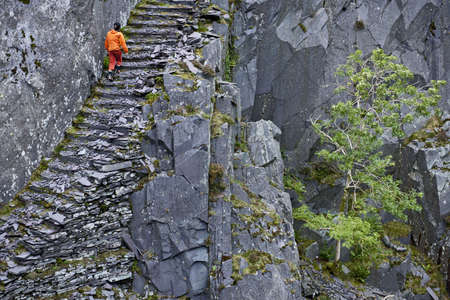 ascends: Climber climbing stairs in rocky cliff