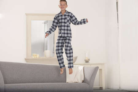 mischeif: Boy in pajamas jumping on couch LANG_EVOIMAGES