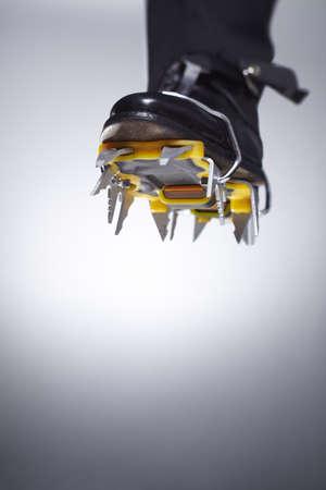 crampon: Businessman wearing spikes on shoe LANG_EVOIMAGES