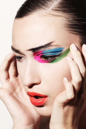 Woman smudging bright coloured make up on face LANG_EVOIMAGES