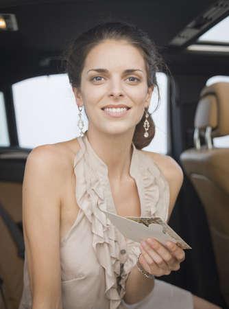 Woman holding letter in backseat of car LANG_EVOIMAGES