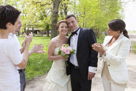 accomplishes: Friends applauding newlywed couple LANG_EVOIMAGES