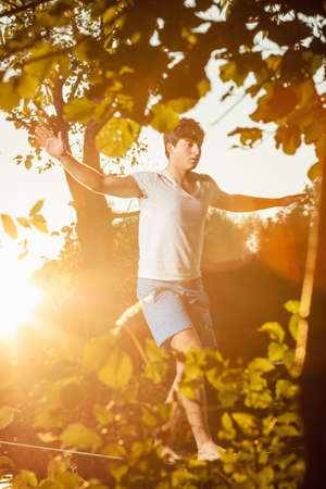 Man walking on tight rope outdoors LANG_EVOIMAGES