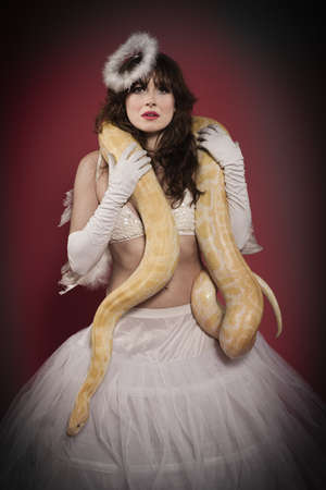 Woman in angel costume wearing snake