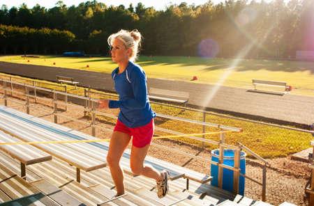 scaling: Woman running up bleacher steps LANG_EVOIMAGES