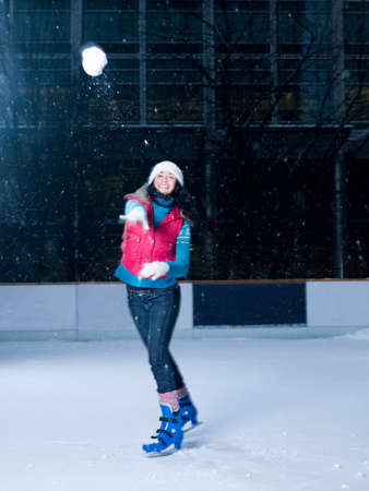 Woman throwing a snowball on an ice rink LANG_EVOIMAGES