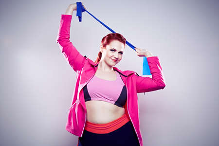 Young woman wearing pink top,stretching elastic