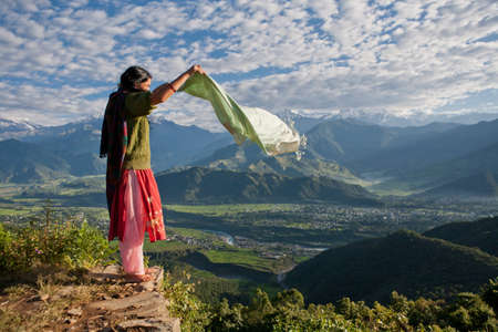 secluded: Nepalese woman holding scarf on cliff edge LANG_EVOIMAGES