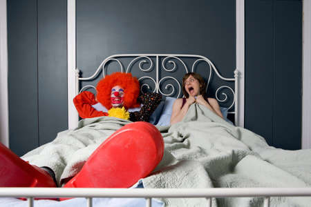 Woman screaming as she realises she is in bed with a clown LANG_EVOIMAGES