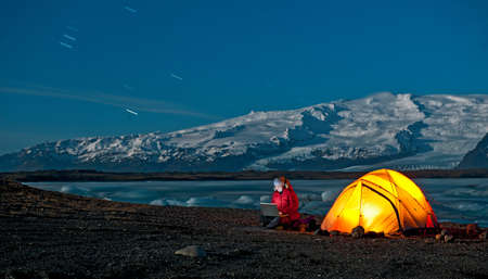 Woman using laptop outside tent,Jokulsa Loni,Iceland LANG_EVOIMAGES