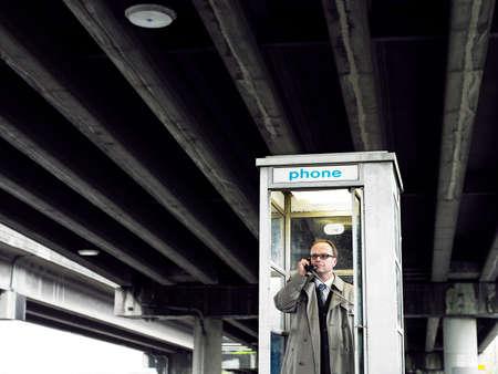 Businessman in telephone booth under bridge