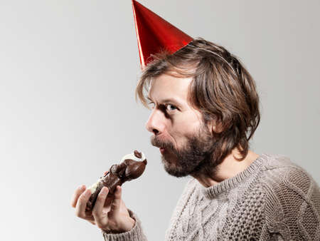 unhealthiness: Mid adult man in party hat eating chocolate against white background