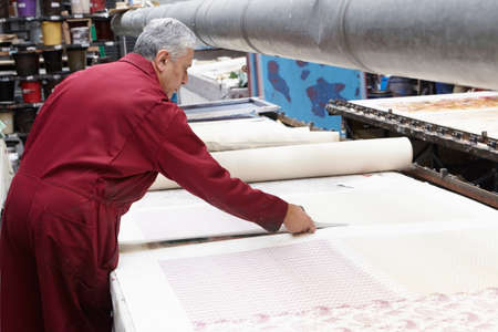 Man cutting fabric in textiles factory