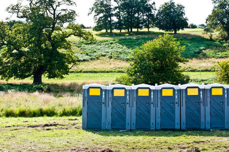 Row of portable toilets in field