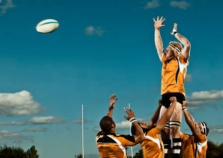 attempt: Rugby player leaping up to catch ball