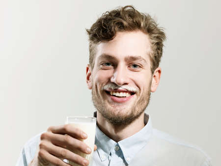 silliness: Young man smiling with milk moustache,studio shot