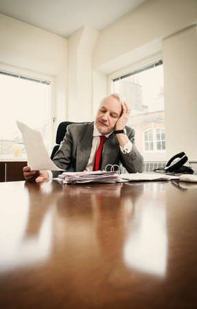 businessman pondering documents: Senior businessman at desk with paperwork and head in hands