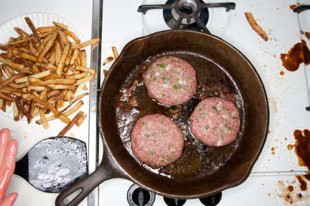 unhealthiness: Burgers cooking in a frying pan