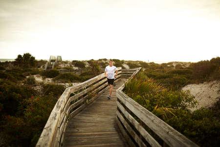 athletic wear: Man running along boardwalk