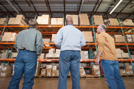 stocktaking: Male warehouse workers looking at cardboard boxes on shelves