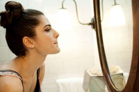 mirror image: Woman looking in bathroom mirror LANG_EVOIMAGES