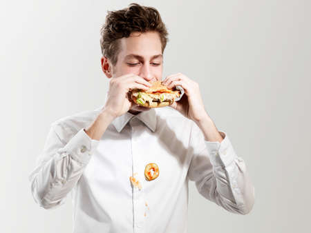 Young man eating messy sandwich,studio shot LANG_EVOIMAGES