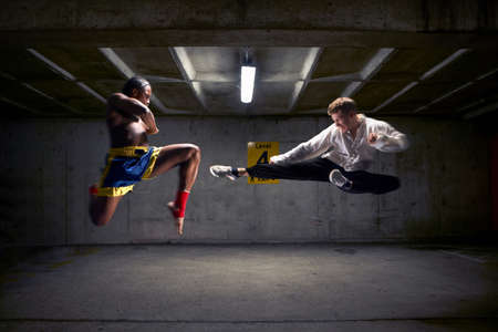 confrontational: Boxer and kick boxer mid air in parking lot LANG_EVOIMAGES
