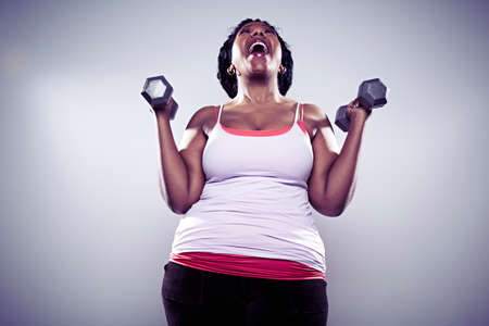 Mature woman using hand weights,laughing