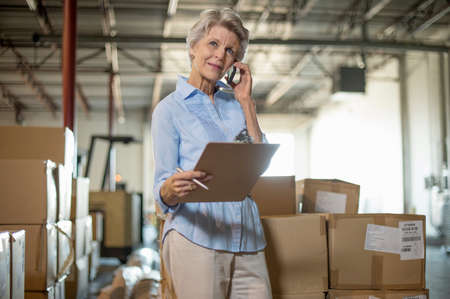 Female warehouse worker holding clipboard LANG_EVOIMAGES