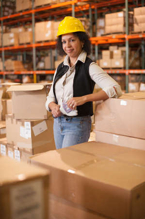 Portrait of female warehouse worker leaning on boxes