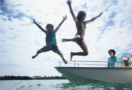 Mother on motorboat,two children jumping into water