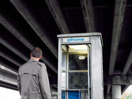 Businessman looking at telephone booth under bridge LANG_EVOIMAGES