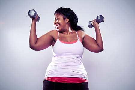 Mature woman using hand weights,smiling LANG_EVOIMAGES