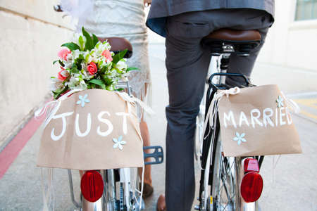 thrifty: Young newlywed couple cycling along street,rear view,close up LANG_EVOIMAGES