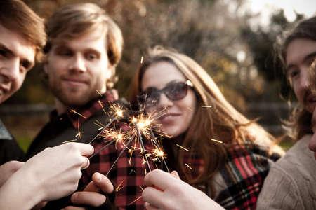 Friends holding sparklers LANG_EVOIMAGES