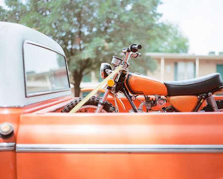 transportation: Orange motorcycle in pick up truck