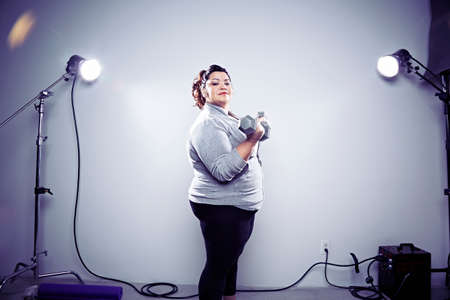 Mid adult woman using hand weights with spot lights