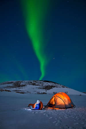 Woman outside tent with Northern lights,Myvatn,Iceland