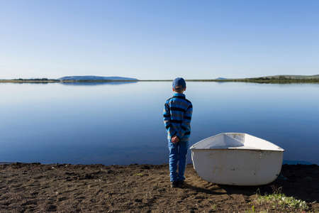 Young boy standing next to rowing boat at lakeside LANG_EVOIMAGES