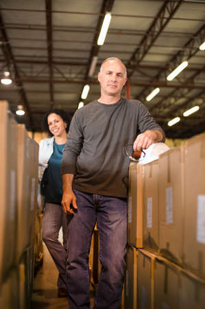 stocktaking: Portrait of warehouse workers by cardboard boxes