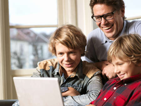 Father watching laptop with sons on sofa