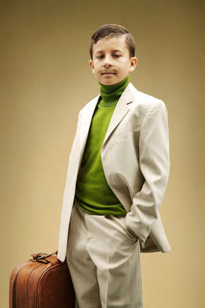 out of context: Young boy dressed in beige suit with fake mustache