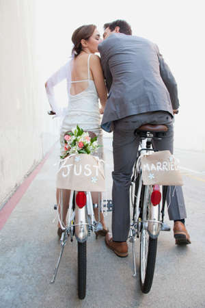economic cycle: Young newlywed couple kissing on bicycles in street