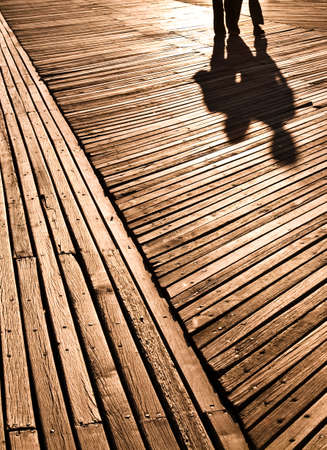 Shadows of two people on boardwalk,Coney Island,New York,USA