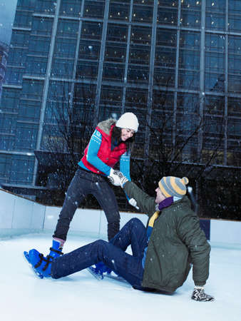 Woman helping man up from ice rink